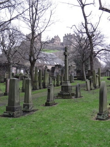 The Edinburgh Castle on the hill behind green graveyards